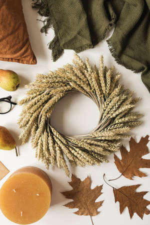 Wreath made of wheat straw, blanket, pillow, glasses, pears, envelop, dry autumn leaves and candle on white background. Fall autumn concept. Flat lay, top view, copy space.