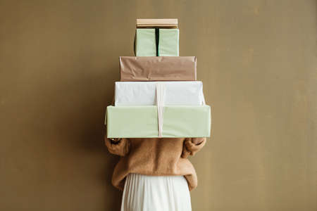 Young beautiful woman hold paper gift boxes stack against olive wall. Festive Christmas / New Year holidays celebration concept.