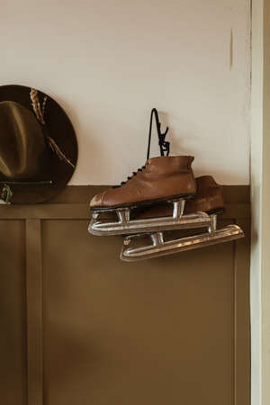 Ice skates and hat hang on the wall. Hipster minimalist concept. Zdjęcie Seryjne