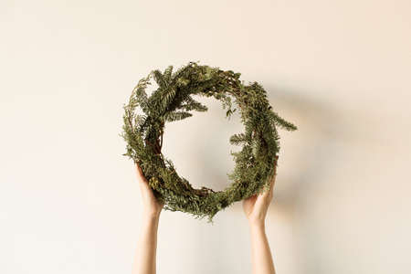 Round wreath frame made of fir and eucalyptus branches in women's hands on neutral background. Christmas / New Year celebration decoration. Holiday concept.