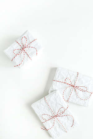 Christmas / New year background. Minimal festive holiday composition. Three gifts wrapped in white paper with red and white rope on white table. Flat lay, top view, copy space.