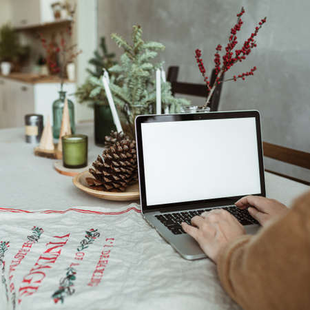 Young woman work on laptop computer with blank display screen with mockup copy space. Kitchen interior with table, Christmas / New Year holidays celebration decorations. Fir branches, cones, candles. Zdjęcie Seryjne