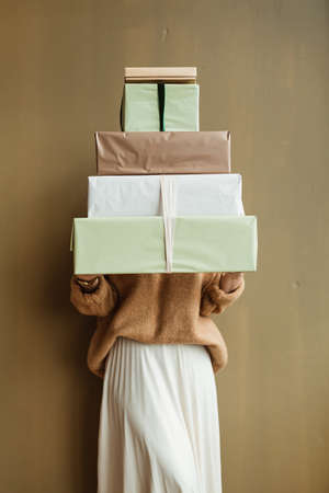 Young beautiful woman holding handmade paper gift boxes stack against olive wall. Minimal fashion festive Christmas / New Year celebration concept.