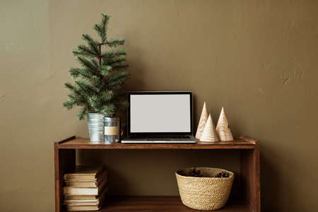 Blank screen laptop with mockup copy space on wooden stand decorated with fir tree, books, straw basket. Minimalist home office desk workspace. Christmas / New Year celebration concept.