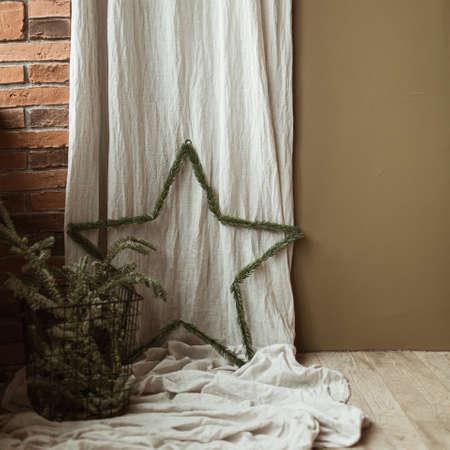 Star symbol decoration made of fir branches on washed linen curtains, fir branches in basket. Minimalist home interior design concept decorated for Christmas celebration.