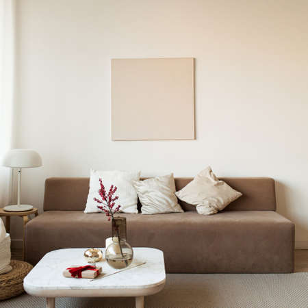 Comfortable modern interior design concept. Sofa, coffee table with decorations, lamp, blank picture frame on the wall.