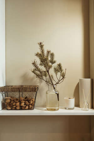 Minimalist kitchen interior design decorated with fir tree branch in vase, basket of walnuts, candle, aroma sticks. Christmas / New Year celebration decorations.