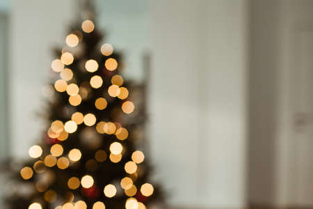 Blurred light on Christmas tree. Bright glow gold bokeh. Reflections of Christmas lights. Zdjęcie Seryjne