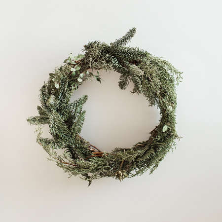 Round wreath frame made of fir and eucalyptus branches on white background. Christmas / New Year celebration decoration. Holiday concept. Zdjęcie Seryjne