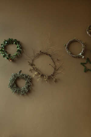 Round homemade wreath frames made of fir needles and branches on olive wall. Christmas celebration decoration. New Year composition. Zdjęcie Seryjne
