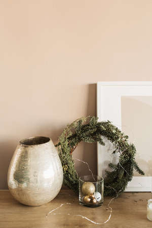 Christmas fir wreath frame, golden baubles, vase, frame on beige wall. Minimalist home interior design concept. Christmas, New Year holidays celebration decorations.