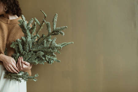 Young beautiful woman in sweater and skirt holding fir branches against olive wall. Minimalist fashion festive Christmas / New Year concept.