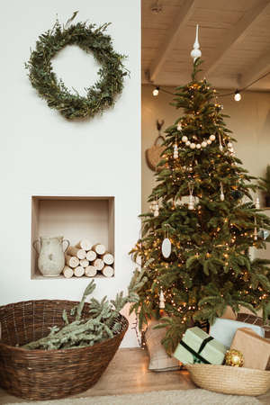 Beautiful Christmas tree, wreath frame, gift boxes in cozy comfortable living room. Festive Christmas / New Year holidays celebration decorations in modern interior design.