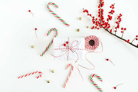 Christmas gift box with festive candies, branch with red berries, reel of christmas rope on white table. Christmas, new year composition. Minimal concept. Flat lay, top view Zdjęcie Seryjne
