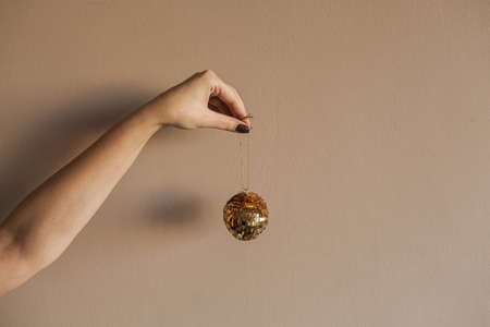 Female hand gold sparkling glossy golden bauble on beige background. Minimal Christmas / New Year holidays celebration decoration.