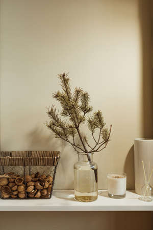 Minimalist kitchen interior design decorated with fir branch in glass vase, basket of walnuts, candle, aroma sticks. Christmas / New Year celebration decorations. Zdjęcie Seryjne