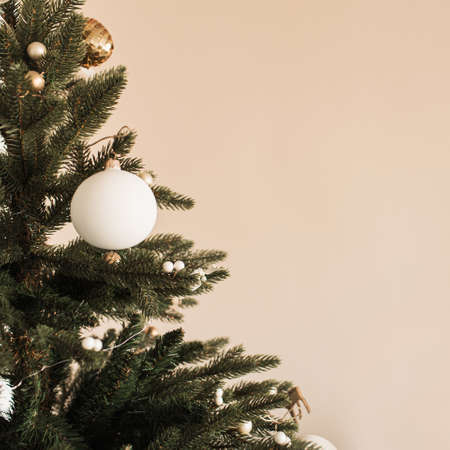 Closeup of Christmas / New Year fir tree decorated with baubles. Holiday celebration composition on beige background.