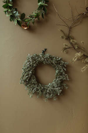 Round homemade wreath frames made of fir needles and branches on olive wall. Christmas / New Year celebration decorations.