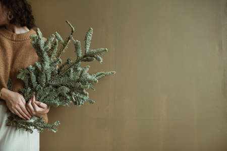 Young beautiful woman in sweater and skirt holding fir branches against olive wall. Minimalistic festive Christmas / New Year concept. Zdjęcie Seryjne
