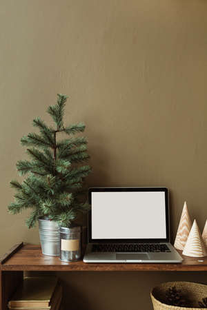 Blank screen laptop computer on wooden stand decorated with fir tree, books, straw basket. Minimalist home office desk workspace. Zdjęcie Seryjne
