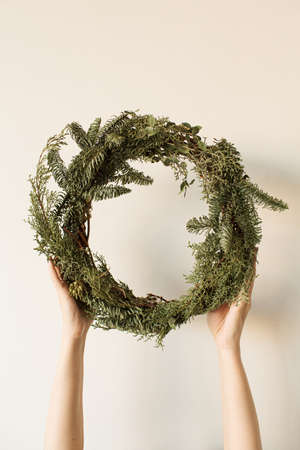 Female hands holding round wreath frame made of fir and eucalyptus branches on neutral background. Christmas / New Year celebration decoration. Holiday concept.