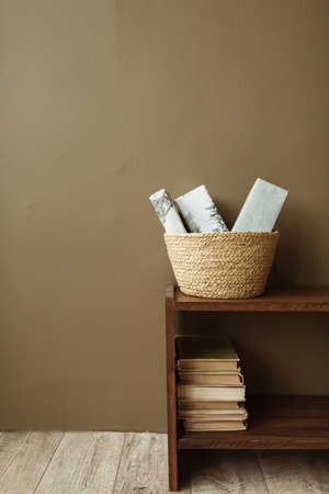 Handmade paper gift boxes in straw basket on wooden stand with books. Minimalist interior design concept.