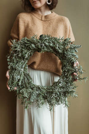 Young beautiful woman in sweater and skirt holding round wreath frame made of fir branches against olive wall. Minimal fashion festive Christmas / New Year celebration concept. Zdjęcie Seryjne