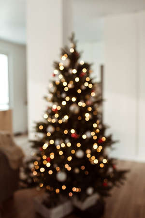 Blurred lights on Christmas tree. Bright glow gold bokeh. Reflections of Christmas lights.