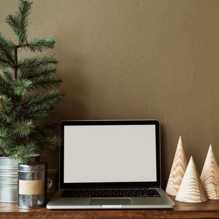 Blank screen laptop with mockup copy space on wooden stand decorated with fir tree. Minimalist home office desk workspace. Christmas / New Year celebration concept.