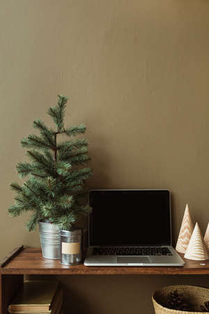 Blank screen laptop with mockup copy space on wooden stand decorated with fir tree. Minimalist home office desk workspace. Zdjęcie Seryjne