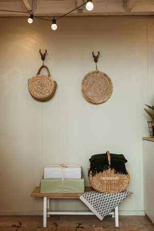 Cozy home interior design concept with rattan bag, straw bags, handmade paper gift boxes against olive wall.