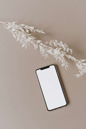 Blank screen mobile phone, white floral branch on neutral pastel beige background. Flat lay, top view minimalist lifestyle blog, website template. Copy space mockup.