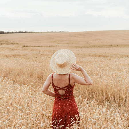 Young girl in red dress and with straw hat standing in rye / wheat field. Summer concept. Stock fotó