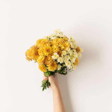 Flatlay of yellow and ginger fall wild flowers bouquet in women's hand isolated on white background. Flat lay, top view minimalistic floral composition. Valentine's Day, Mother's Day concept.