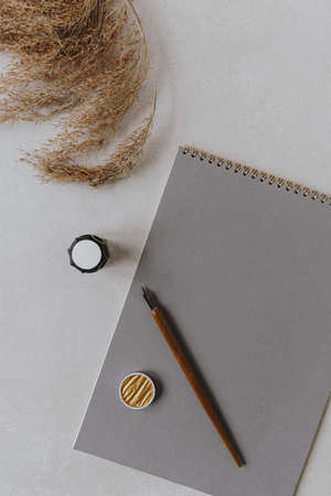 Lettering, handwriting artist concept with blank paper sheet notebook, pen, ink, fluffy reeds on gray background. Flatlay minimalist stylish workspace desk. Top view copy space mock up.