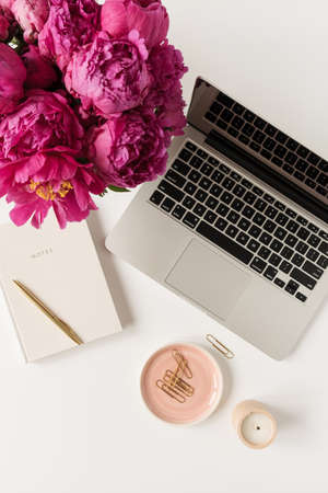 Home office desk workspace with laptop, pink peony flowers bouquet and notebook on white background. Flat lay, top view freelance work concept.