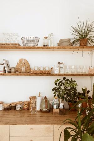 Modern boho style home kitchen interior concept. Wooden shelfs, dishes, utensils, decorations. Cozy comfortable bohemian interior design.