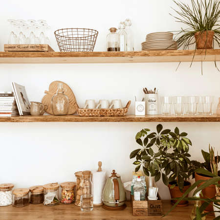 Stylish boho home kitchen interior concept. Wooden shelfs, dishes, utensils, glasses, decorations. Cozy comfortable interior design.