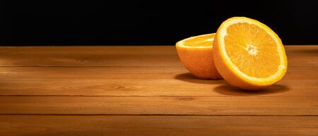 Halves oranges on a black background. Space for text. Sliced citrus fruits on a wooden table.