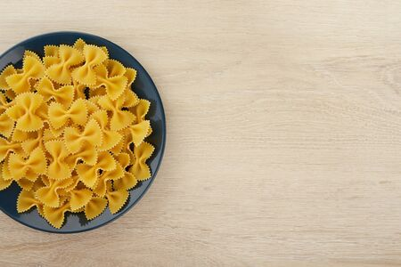 Raw pasta in the shape of a bow on a plate, top view, copy space Zdjęcie Seryjne
