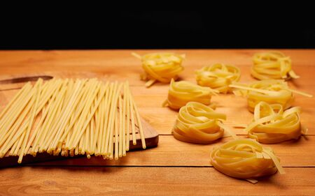 Raw uncooked pasta on the rustic wooden table