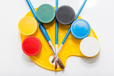 Colorful jars of paints and brushes on the yellow palette photo