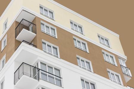 Apartment block under abstract brown sky. Isolated. Bottom view. Concept: life, couple, family, kids, independence.