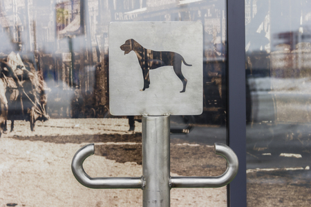 Place with sign for dogs waiting for the owner near the shopping mall. Concept: safety, law, devotion.