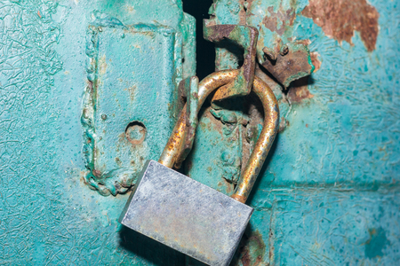 The padlock on the metal green door. Concept: safely, storage, security Standard-Bild