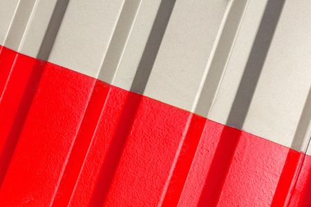 The two halves grey and red of the figure of corrugated texture. Concept: reliable, abstract, creative, art, fence. Standard-Bild