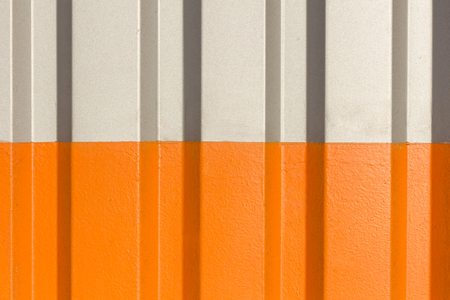 The two halves grey and orange of the figure of corrugated texture. Concept: reliable, abstract, creative, art, fence.