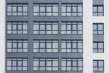 Dark grey facade of building with grey big windows. Standard-Bild