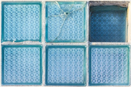 Decorative and glossy glass block window in blue as a texture or for background. Broken place. The wall. Geometric background.
