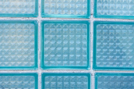 Decorative and glossy glass block window in blue as a texture or for background. The wall. Geometric background.